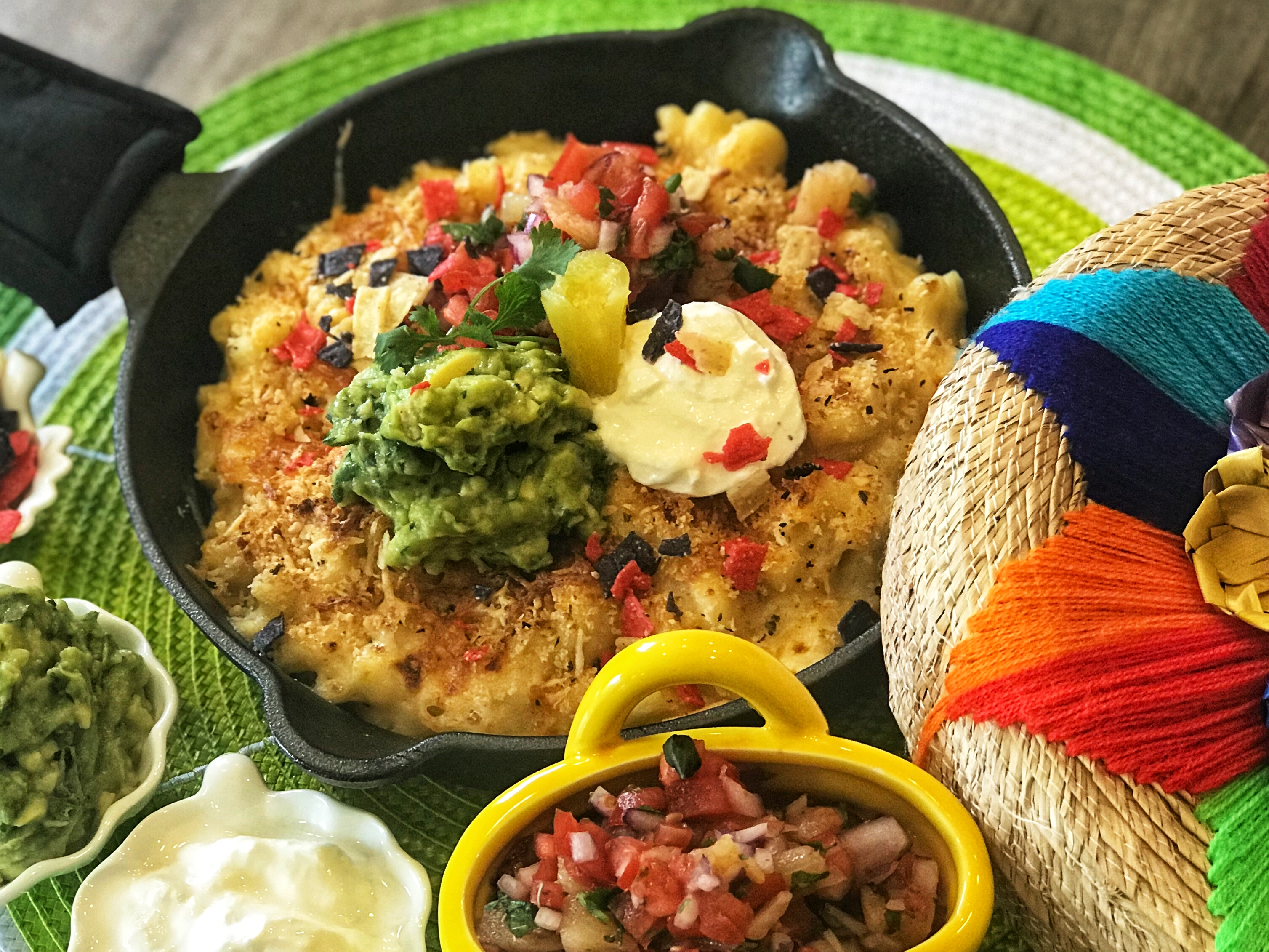 Mac 'n Cheese, the way our family likes it; with a Mexican twist - baked with guacamole, pineapple pico de gallo, sour cream and topped with infused breadcrumbs! The cheese sauce is really just original, made with cheddar and parmesan.
